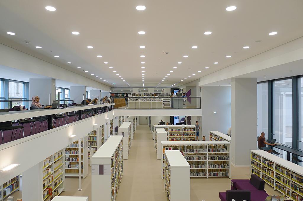 Die mehrgeschossige Bibliothek als Einraum, Bezüge zum Außenraum vervollständigen diesen Eindruck.