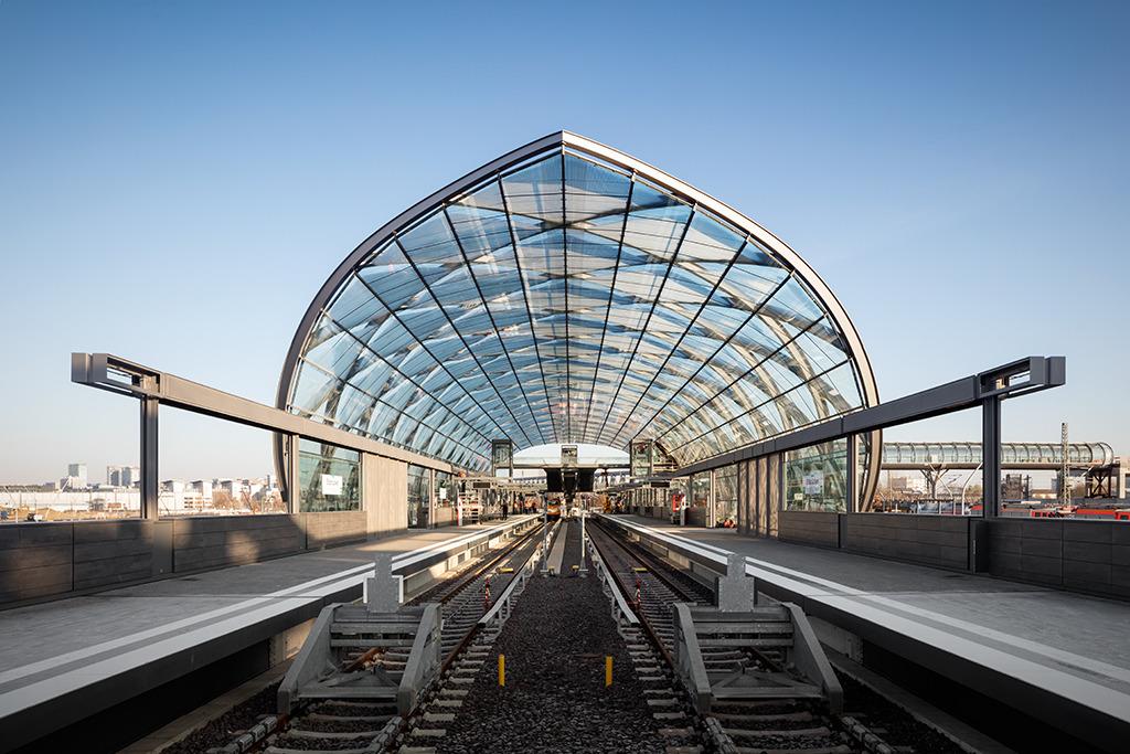 """Empgangsgeste für die einfahrenden Bahnen (Bild: Marcus Bredt) Realisierungswettbewerb, Einladungswettbewerb 2012 - 1. Preis (2013) U-Bahnhaltestelle der U4 an den Elbbrücken mit Anbindung an die S-Bahnhaltestelle. Das Quartier """"Elbbrücken"""" wird den östlichen Abschluss der Hafencity bilden. Um dieses auch effektiv an den öffentlichen Nahverkehr anzuschließen, wird die U-Bahnlinie U4 bis zu den Elbbrücken verlängert. Die tonnenförmige Dachkonstruktion der dort geplanten Haltestelle wird durch gekreuzte, bogenförmige Rahmen gebildet. Die hierdurch entstehende optische Präsenz des Tragwerks wird durch die nach innen abgehängte Verglasung unterstrichen. Die kreuzförmige Anordnung der Rahmen ergeben ein rostartiges System, wodurch eine gegenseitige Stabilisierung der stählernen Bögen gegeben ist. Die lichtdurchflutete Haltestelle ermöglicht so diverse Ausblicke zu den markanten Hochhäusern und zu den Elbbrücken. Entwurf: Volkwin Marg und Jürgen Hillmer mit Stephanie Joebsch Partner: Jürgen Hillmer Projektleitung: Stephanie Joebsch Tragwerksplanung: schlaich bergermann partner Bauherr: Hamburger Hochbahn AG"""