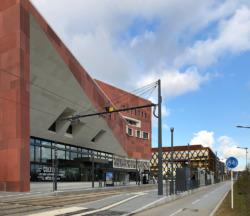 Die Tramhaltestelle liegt prompt vor dem Bibliothekseingang, obendrein stört eine der ordinären Werbeleuchtkästen den ambitioniert begonnen öffentlichen Raum. (Bild: Ursula Baus)