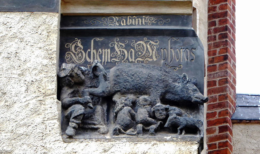 Das Sandsteinrelief zeigt eine Sau, an deren Zitzen Menschen saugen, die Juden darstellen sollen. Ein Rabbiner blickt dem Tier unter den Schwanz. Mit solchen Darstellungen sollten Juden im Mittelalter davon abgeschreckt werden, sich in der jeweiligen Stadt niederzulassen. Ähnliche Spottplastiken finden sich auch am Kölner und Regensburger Dom sowie am Dom zu Brandenburg. (Bild: Wolfgang Kil)