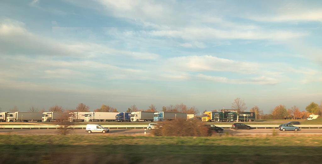Unterwegs im Zug: Autobahnen und Parkplätze säumen die Strecken. (Bild: Ursula Baus)