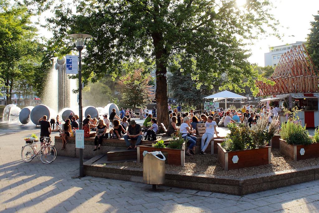 Sommerliche Atmosphäre am Platz mit wasserkinetischer Plastik und Gastronomie im Hintergrund. (Bild: Stadt Köln)